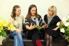 Drei Frauen sitzen auf Couch und stöbern Journal durch Lizenzfreie Stockfotografie