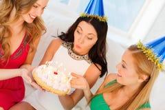 Drei Frauen, welche die Hüte halten Kuchen mit Kerzen tragen lizenzfreie stockfotos