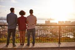 Drei Freunde auf einer Brücke, die heraus schaut lizenzfreie stockfotografie