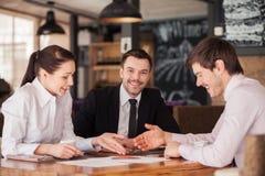 Drei Freunde besprechen das Diagramm, das auf Tabelle am Café liegt stockfotografie