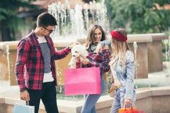 Drei Freunde, die in der Hand farbige Einkaufstaschen halten Stockbilder
