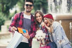 Drei Freunde, die in der Hand farbige Einkaufstaschen halten Stockbild