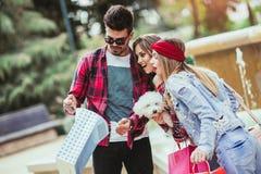 Drei Freunde, die in der Hand farbige Taschen halten Stockfotografie
