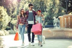 Drei Freunde, die in der Hand farbige Taschen halten Lizenzfreie Stockfotografie