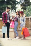 Drei Freunde, die in der Hand farbige Taschen halten Lizenzfreies Stockbild