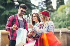 Drei Freunde, die in der Hand farbige Taschen halten Lizenzfreies Stockfoto