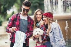 Drei Freunde, die in der Hand farbige Taschen halten Stockbild