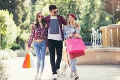 Drei Freunde, die in der Hand farbige Taschen halten Stockfotos