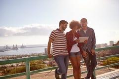 Drei Freunde, die an einem Geländer sich lehnen lizenzfreie stockfotografie