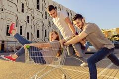 Drei Freunde, die Einkaufslaufkatze mit einem Mädchen in ihr drücken lizenzfreie stockfotografie