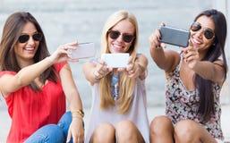 Drei Freunde, die Fotos mit einem Smartphone machen Stockfotos