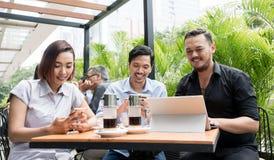 Drei Freunde, die Geräte verwenden, schlossen an das drahtlose Internet n an Stockbild