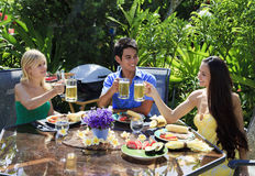 Drei Freunde, die Grill zu Mittag essen Stockfotos