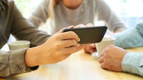 Drei Freunde, die Medieninhalt mit einem intelligenten Telefon teilen stock video footage