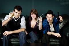 Drei Freunde, die mit Getränken partying sind Stockfotos