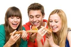 Drei Freunde, die Pizza essen Stockfotografie
