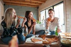 Drei Freunde, die Pizza im Haus essen lizenzfreie stockfotos