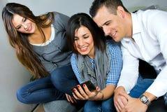 Drei Freunde, die Spaß mit einem Handy haben Lizenzfreie Stockfotos