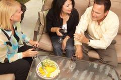 Drei Freunde, die Wein auf dem Patio genießen stockfotos
