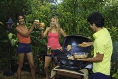 Drei Freunde an einem Grill Stockbild