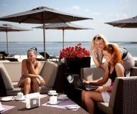 Drei Freunde in einem Kaffee auf dem Strand lizenzfreie stockfotografie