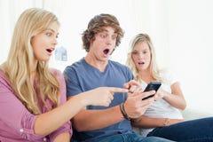 Drei Freunde entsetzt an der Mitteilung am Telefon Stockbild