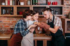 Drei Freunde genießen Geruch der frisch gebackenen Pizza lizenzfreies stockfoto