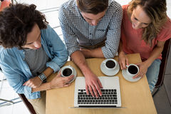 Drei Freunde mit Kaffeetassen unter Verwendung eines Laptops Stockbild