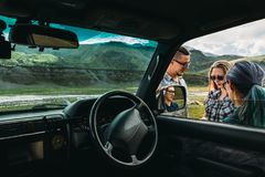 Drei Freunde nahe dem Auto besprechen den Weg in der Reise lizenzfreie stockfotos