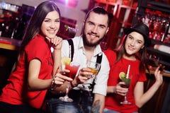Drei Freunde - netter Kerl und zwei attraktive junge Mädchen an einer Partei, die Cocktails vor einem Barlächeln hält Stockbild