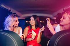 Drei Freunde sitzen zusammen im Auto Blonde und Brunettemädchen betrachten einander Sie haben Bananen herein Lizenzfreies Stockfoto