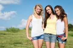 Drei Freundinnen in der kurzen Jeanshose über blauem Himmel Lizenzfreie Stockbilder