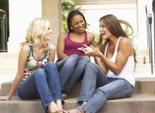 Drei Freundinnen, die auf Jobstepps des Gebäudes sitzen Stockfotografie