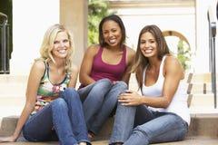 Drei Freundinnen, die auf Jobstepps des Gebäudes sitzen Lizenzfreies Stockbild