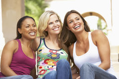 Drei Freundinnen, die auf Jobstepps des Gebäudes sitzen Stockfoto