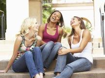 Drei Freundinnen, die auf Jobstepps des Gebäudes sitzen Lizenzfreies Stockfoto