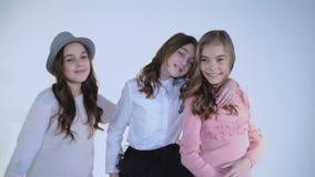 Drei Freundinnen, die an der Kamera lächeln, umfassen und sich freuen stock footage