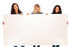 Drei Freundinnen, die eine leere Anschlagtafel und ein Lächeln halten Stockfoto