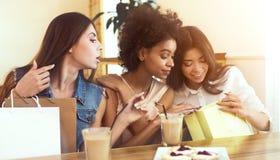 Drei Freundinnen, die im Caf? mit Einkaufstaschen sitzen stockfotos