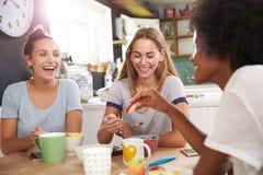 Drei Freundinnen, die zu Hause Frühstück zusammen genießen stockbild