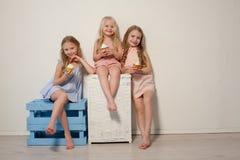 Drei Freundinschwestern essen süße Lutschersüßigkeit lizenzfreie stockfotografie