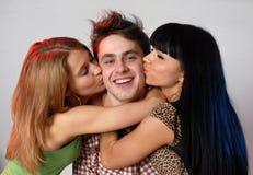 Drei freundliche lächelnde junge Leute Lizenzfreie Stockfotos
