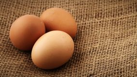 Drei frische braune Hühnereien, die auf Leinwandgewebehintergrund sich drehen stock video footage