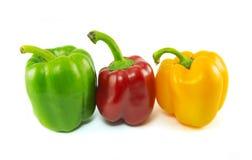 Drei frische Gemüsepaprikas lokalisiert auf weißem Hintergrund Lizenzfreie Stockfotos