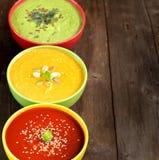 Drei frische Suppen auf einem Holztisch Lizenzfreie Stockfotos