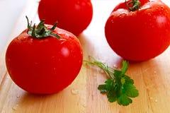 Drei frische Tomaten mit Wassertropfen auf ihnen Stockfoto