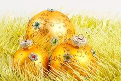 Drei gelbe Weihnachtskugeln im gelben Filterstreifen lizenzfreies stockfoto