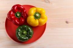 Drei Gemüsepaprikas, Holztischhintergrund lizenzfreie stockfotos