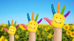 Drei gemalte Hände Familie auf Sonnenblumenfeld Stockfotografie