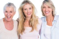 Drei Generationen von den netten Frauen, die an der Kamera lächeln Stockbild